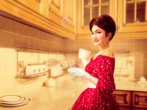 Attractive pinup girl with make-up on the kitchen. Attractive pinup girl with make-up drinks coffee on the kitchen cafe, 50 american fashion. Red dress with Royalty Free Stock Photo