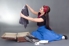 Beautiful pinup girl packing retro suitcase Royalty Free Stock Photo