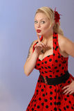 Attractive pinup girl in red polka-dot dress. Fifties style attractive blond pinup girl in red polka-dot dress gestures with finger - humorous pose royalty free stock photos