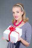 Attractive pinup girl in striped dress with gift Stock Image