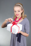 Attractive pinup girl in striped dress opening gift Royalty Free Stock Images