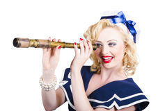 Attractive pinup sailor girl with a monocular. Happy blond American retro style pinup sailor girl holding monocular on white background Royalty Free Stock Photography