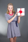 Attractive pinup woman in striped dress with gift over grey Stock Photography