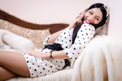 Attractive pinup woman talking on the mobile cell phone looking at camera & happy smiling sitting on sofa Stock Photo