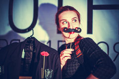 Attractive playful beautiful young woman holding mustache on a stick Stock Image