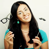 Attractive playful young woman holding mustache and glasses on a Stock Image