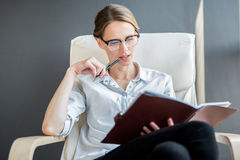 Attractive pleasant lady holding journal pensively Royalty Free Stock Photography