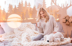 Attractive pleasant woman having tea. Joy and happiness. Attractive nice pretty woman sitting on the bed and having tea while stroking her stuffed bear Royalty Free Stock Images