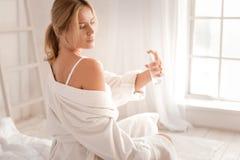 Attractive pleasant woman using body spray royalty free stock photos