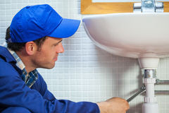 Attractive plumber repairing sink Stock Photos