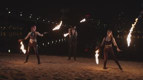 Trio of artists spinning fire poi on river bank stock footage