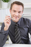 Attractive positive business man at office. Royalty Free Stock Image