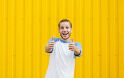 Happy man giving thumbs up on a wall background. Smiling cute guy. Success concept. Copy space. Attractive and positive guy with stylish haircut showing two Royalty Free Stock Image