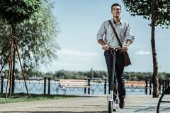 Attractive positive guy testing new electric scooter royalty free stock image