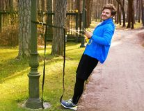 A man exercising in a park with trx fitness strips. Attractive positive male in a blue raincoat exercising in a park with trx fitness strips Stock Photography