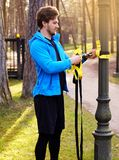 A man exercising in a park with trx fitness strips. Attractive positive male in a blue raincoat exercising in a park with trx fitness strips Royalty Free Stock Photography