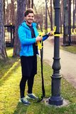 A man exercising in a park with trx fitness strips. Attractive positive male in a blue raincoat exercising in a park with trx fitness strips Royalty Free Stock Image