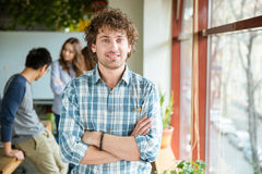 Attractive positive male with folded hands standing near the window Stock Image