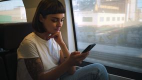 Activity in train. Attractive positive woman in white tshirt and jeans, chats on messaging application or plays online game, she sits in fast moving high speed stock footage