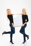 Attractive positive young blonde sisters twins posing with blank board Stock Photo