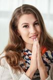 Namaste. Attractive positive young woman holding her hands in namaste gesture stock image