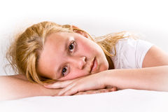 Attractive pre-teen looking at viewer. Attractive pre-teen girl looking intensely at viewer, laying down Stock Image
