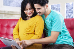 Attractive pregnant couple playing tablet Stock Images