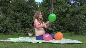 Attractive pregnant woman girl blow colorful balloons in garden Stock Photo