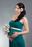 Attractive pregnant woman in green dress with flowers dreaming o Stock Images