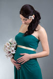 Attractive pregnant woman in green dress with flowers over grey Stock Photos