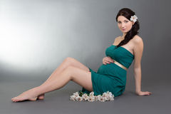 Attractive pregnant woman in green dress with flowers sitting ov Stock Photo
