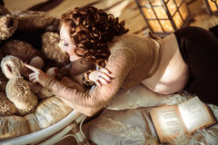 Attractive pregnant woman lying on fur with a book and touching. Plush toys on the wooden background Stock Images