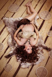 Attractive pregnant woman lying on fur. With a book on the wooden background Stock Images