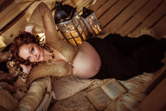 Attractive pregnant woman lying on fur with a book. In a wooden house. Top view Royalty Free Stock Image