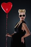Attractive pregnant woman with a red balloon. Royalty Free Stock Image