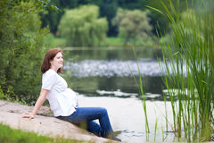 Attractive pregnant woman relaxing at lake shore Stock Image