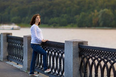 Attractive pregnant woman relaxing in park at river shore Stock Photo