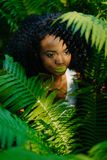 The attractive pretty african girl with green eyeshadows and lipstick is surrounded by green ferns. No look in camera Royalty Free Stock Photos