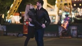 Attractive pretty couple spends date night at amusement park at night stock footage
