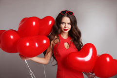 Attractive pretty girl in love, portrait of brunette woman in re. D with heart balloons isolated on gray studio background. Valentine day. Birthday party Stock Photo