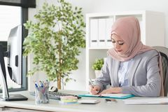 Attractive pretty muslim woman manager using pen