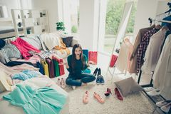 Attractive pretty nice funny cheerful cheery girl sitting on floor among different clothes making choice what to put on. In light white interior dressing room stock photos