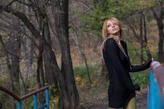 Attractive pretty woman posing on the autumn bridge Royalty Free Stock Image