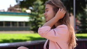 Lovely teenage girl with straight long blonde hair sitting in parkland stock footage