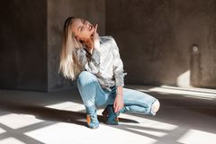 Attractive pretty young sexy woman in a fashionable shirt in blue ripped jeans in green cowboy boots sits on a sunny spring day. Indoors. Sensual beautiful royalty free stock photo