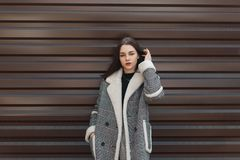 Attractive pretty young woman in an elegant checkered coat with white fur in a black stylish t-shirt in gray pants posing. Against a metal wall. Fashionable stock photos