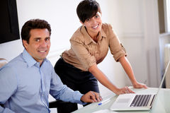 Attractive professional couple smiling at you Royalty Free Stock Photography