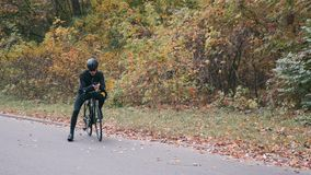 Attractive professional male cyclist in cycling apparel with road bike standing in fall city park and typing mail on smartphone. M. An cycling. Autumn outdoor stock video footage