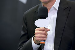Attractive professional male news reporter holding microphone. Talking to camera live broadcasting Royalty Free Stock Photo