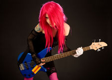Attractive punk girl with bass guitar. Attractive rock girl in crazy outfit with bass guitar stock photo